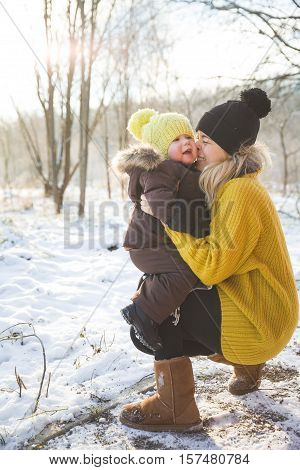 Happy family. Young beautiful mother hugging her cute little toddler boy while walking in a winter park on a cold sunny day. Mom with child outdoors.