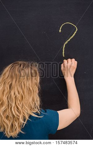 Young girl drawing question mark on a black background. Business woman drawing question mark on the board. Teacher hand drawing question mark on chalkboard. Education and idea concept.