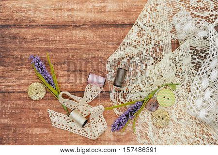 Piece of lace fabric with reel of thread, buttons and artificial lavander twig lying on wooden background. Scrapbooking materials. Copy space. Texture.