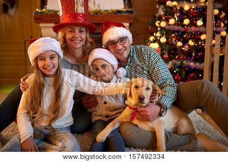 Portrait of a happy family and the dog spending together Christmas time at home