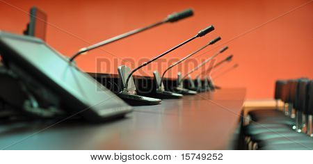 Conference table microphones and office chairs close-up