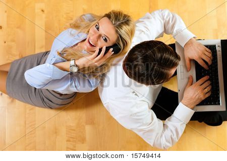 Businesspeople sitting on the floor at home working with laptop computer and telephone
