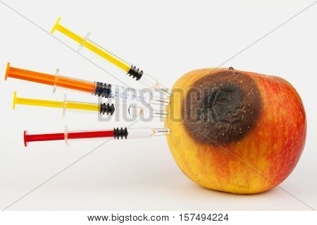 Moldy apple. Injection into red apple - Concept for Genetically modified fruit and syringe