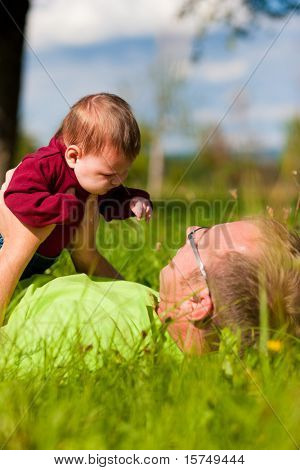 Father playing with his baby child on a great sunny day in a meadow with lots of green grass and wild flowers