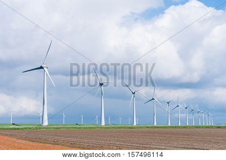 row wind turbines in an agricultural dutch landscape