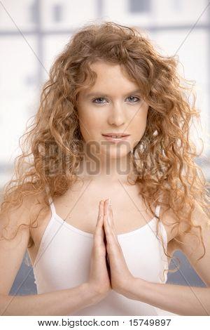 Hübsche junge Frau praktizieren Yoga, Meditation, im Gebet Pose, die Augen offen, auf Fußboden.?