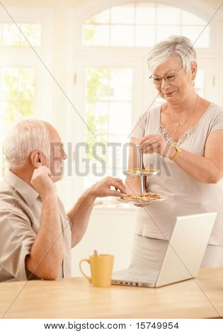 Smiling wife serving cookies in kitchen to husband sitting with laptop computer and coffee.?