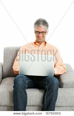 Mid-adult man wearing jeans and orange shirt sitting on couch, using laptop computer. Isolated on white.?