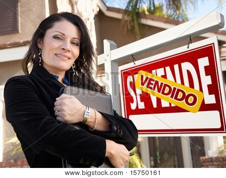 Proud, Attractive Hispanic Female Agent In Front of Spanish Vendido Se Vende Real Estate Sign and House.