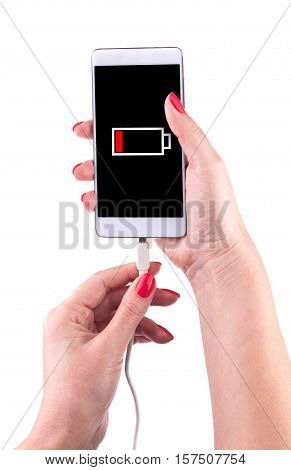 Female hand holding low battery smartphone and connect charger isolated on white background