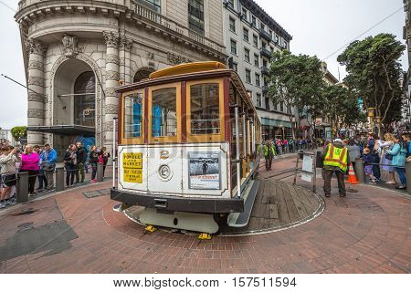 San Francisco, CA, USA - August 15, 2016: Cable car operators push the turntable around the reverse direction in Powell and Market St Turntable or terminus while crowds of tourists waiting to go up.