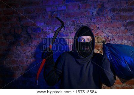Night gangster near brick wall