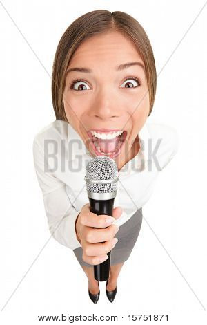 Businesswoman screaming / talking in microphone. Funny photo of young casual business woman holding microphone. Asian Caucasian female model isolated on white background.