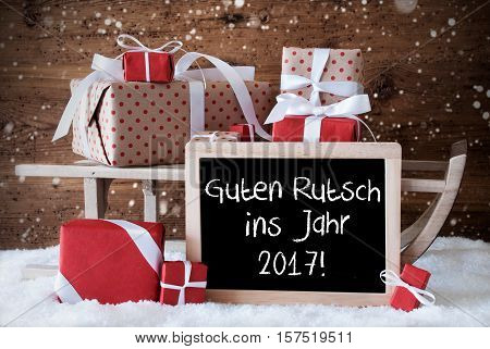Chalkboard With German Text Guten Rutsch Ins Jahr 2017 Means Happy New Year. Sled With Christmas And Winter Decoration And Snowflakes. Gifts And Presents On Snow With Wooden Background.