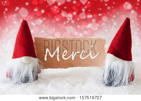 Christmas Greeting Card With Two Red Gnomes. Sparkling Bokeh And Christmassy Background With Snow. French Text Merci Means Thank You