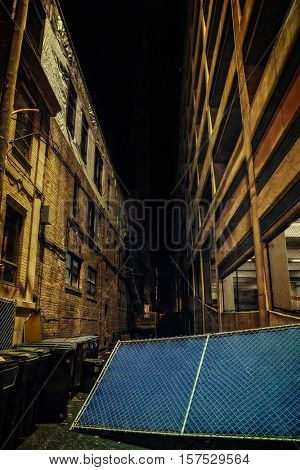 Dark Urban Alley at Night with Fence