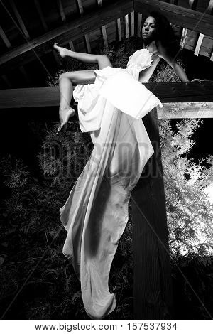 Attractive girl in white long dress poses on wooden beam. Black-white outdoor photo.