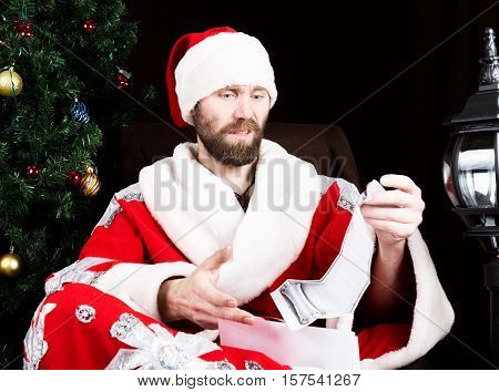 bad brutal Santa Claus discontentedly reads letter with the wishes, on the background of Christmas tree.