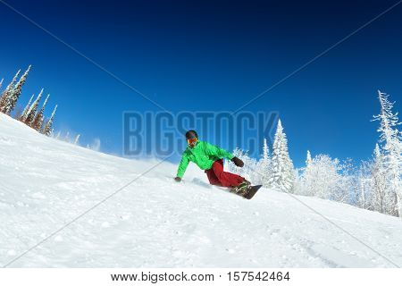 Snowboarder rides on slope. Snowboarding downhill. Ski resort Sheregesh
