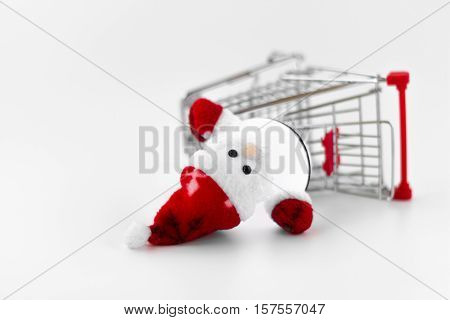 Santa Claus dropped out from the shopping cart. A conceptual representation of wrong gift or forgotten. Of rampant consumerism and the loss of the true spirit of Christmas. Shallow DOF.