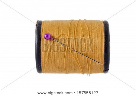A pink sewing pins with brown bobbin thread on white background.