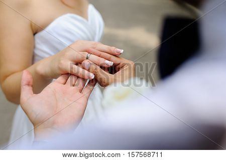 wedding rings in hands of newlyweds close up
