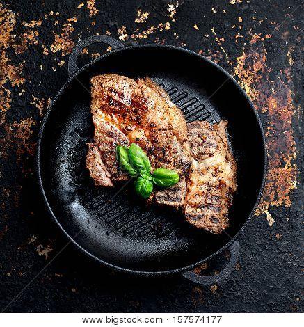 juicy grilled steaks in a frying pan