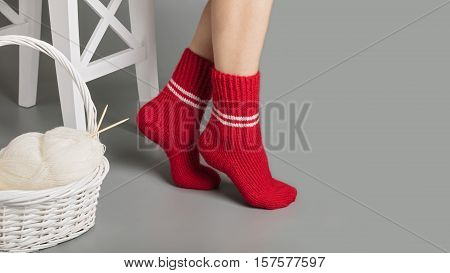 Female feet in red knitted socks near the basket with yarn and knitting.