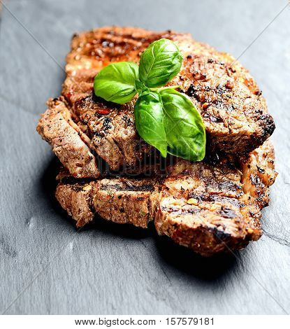 juicy steaks grilled  with aromatic spices on basalt