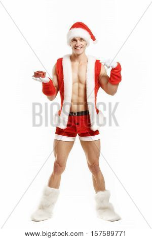 Fitness Santa pointing a red box. Muscular Santa Claus holding a Christmas present in red box. Fitness Santa Happy New Year. Bodybuilder Santa with a red box on white background. Sexy Santa Claus