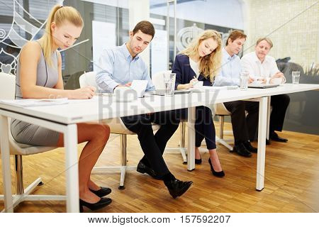 Business people taking a competence test in a business training seminar