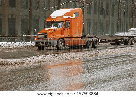 Cargo truck on the urban highway with wall with windows on a background. Truck on the road. Orange truck on the asphalt city road in the evening time.