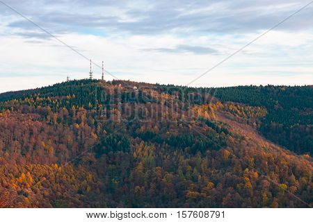 Telecommunication towers on the summit of the hill covered with colorful fall forest