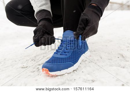 fitness, sport, people, sportswear and footwear concept - close up of man foot and hands tying shoe lace in winter outdoors