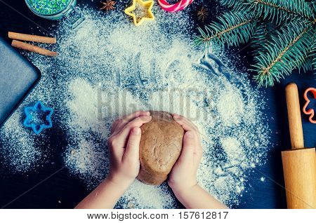 Young girl's hands kneading dough. Christmas baking preparation. Close-up of child's hands baking cookies. Merry Christmas and Happy New Year. Christmas family baking concept. Top view.