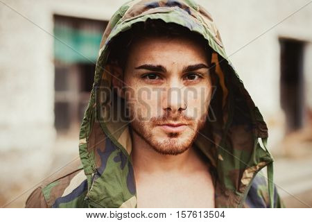 Hooded guy with camouflage jacket in the street