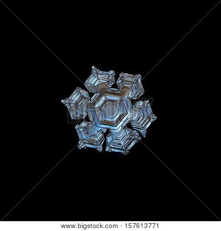 Snowflake isolated on black background. This is macro photo of real snow crystal with glossy surface, six broad arms and large central hexagon with relief details.