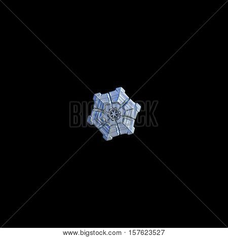 Snowflake isolated on black background. This is real snowflake macro photo: tiny sectored plate snow crystal, captured on glass surface with LED back light.