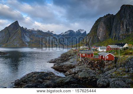 Traditional Norwegian Fishing village rorbuer with Lilandstinden mountain Hamnoy island Reine Lofoten Northern Norway