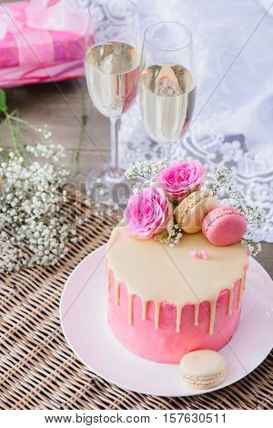 Pink roses and macaroon cookies on top of the pink cake. Sparkling wine and a present box in the background