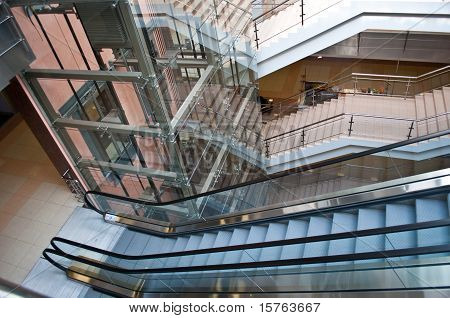 glass elevator shafts escalators and stairs in a modern office building