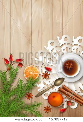 Christmas tea party background. Holiday top view background with cup of tea, tree branches, Rosehip berries, orange, cinnamon sticks and star anise on wooden table