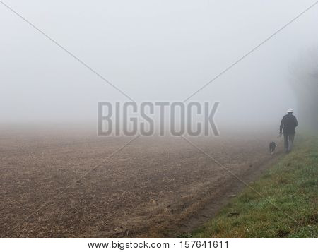 KIRKBY IN ASHFIELD ENGLAND - OCTOBER 31: Man walking dog in fog England. In Kirkby In Ashfield Nottinghamshire England. On 31st October 2016.