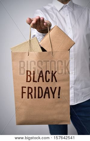 closeup of a young caucasian man with a paper shopping bag full of cardboard boxes in his hand and the text black friday written in it