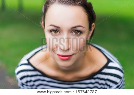 Portrait of a girl closeup cosmetics face light smile red lipstick on the lips expressive eyes brown eyes.