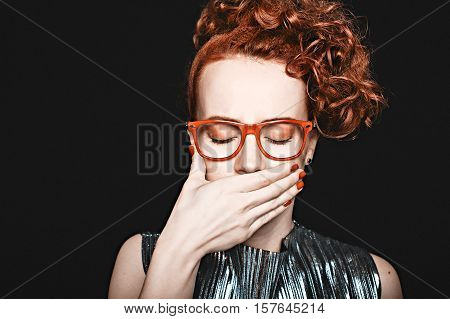 woman covered her mouth with his hand. beautiful red-haired woman with closed eyes in glasses holding her hand to her mouth. black background. closeup. the concept of coping with anxiety