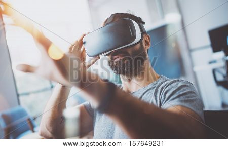 Closeup of bearded young man wearing virtual reality goggles in modern coworking studio. Smartphone using with VR headset. Horizontal, blurred