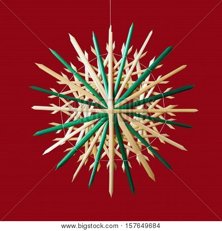 Straw star Christmas decoration on red background. Handmade colorful decor for windows, as gifts or to hang on the xmas tree, traditionally made from natural straw. Macro photo front view close up.