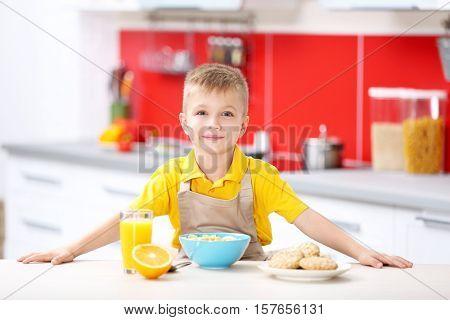 Little boy having breakfast in the kitchen