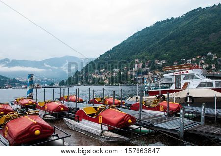 LAKE COMO, LOMBARDY, ITALY - MAY 27, 2010: Row of pedal boats parked at Lake Como surrounded by the beautiful scenery of Como Lake